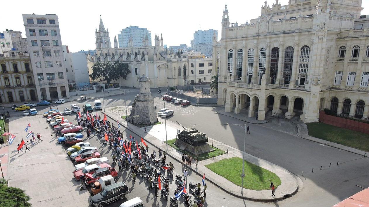 Jugendliche ziehen Fahnen schwingend über einen großen Platz in der kubanischen Hauptstadt