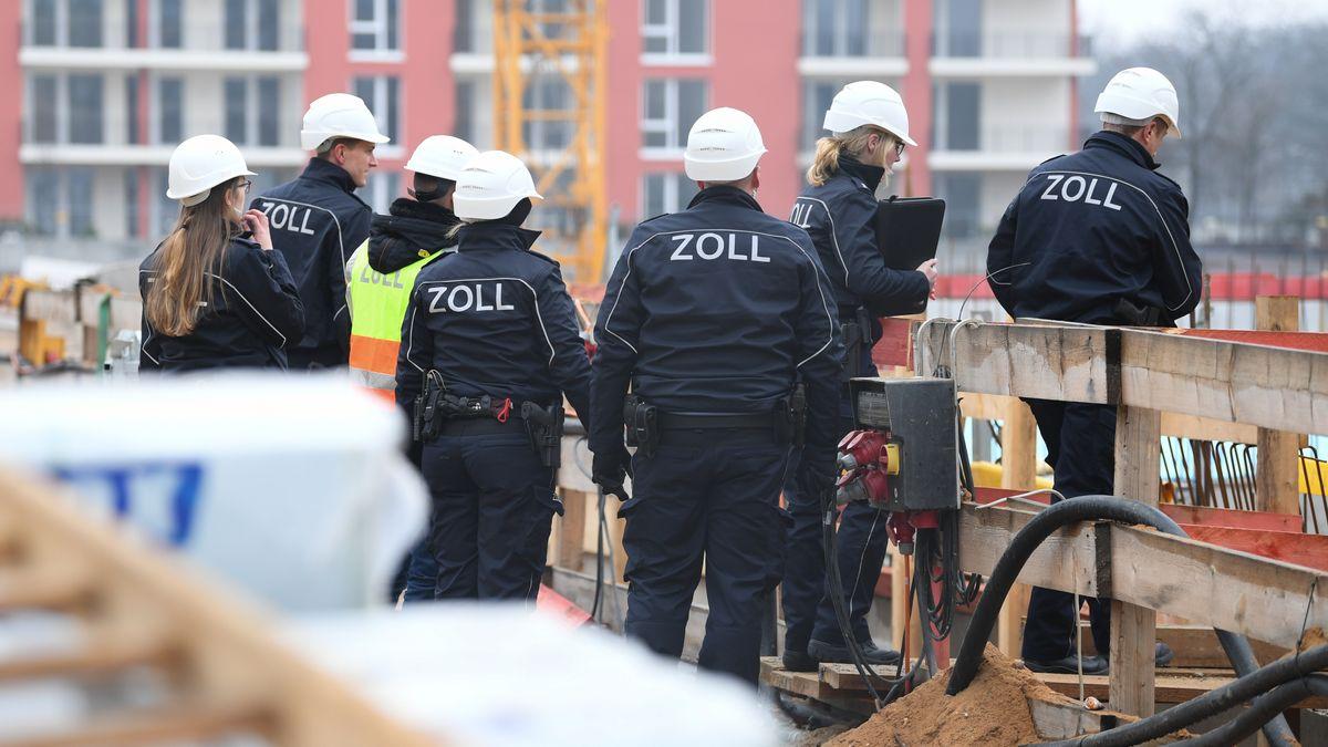 Beamte des Zoll gehen während eines Einsatzes über eine Großbaustelle