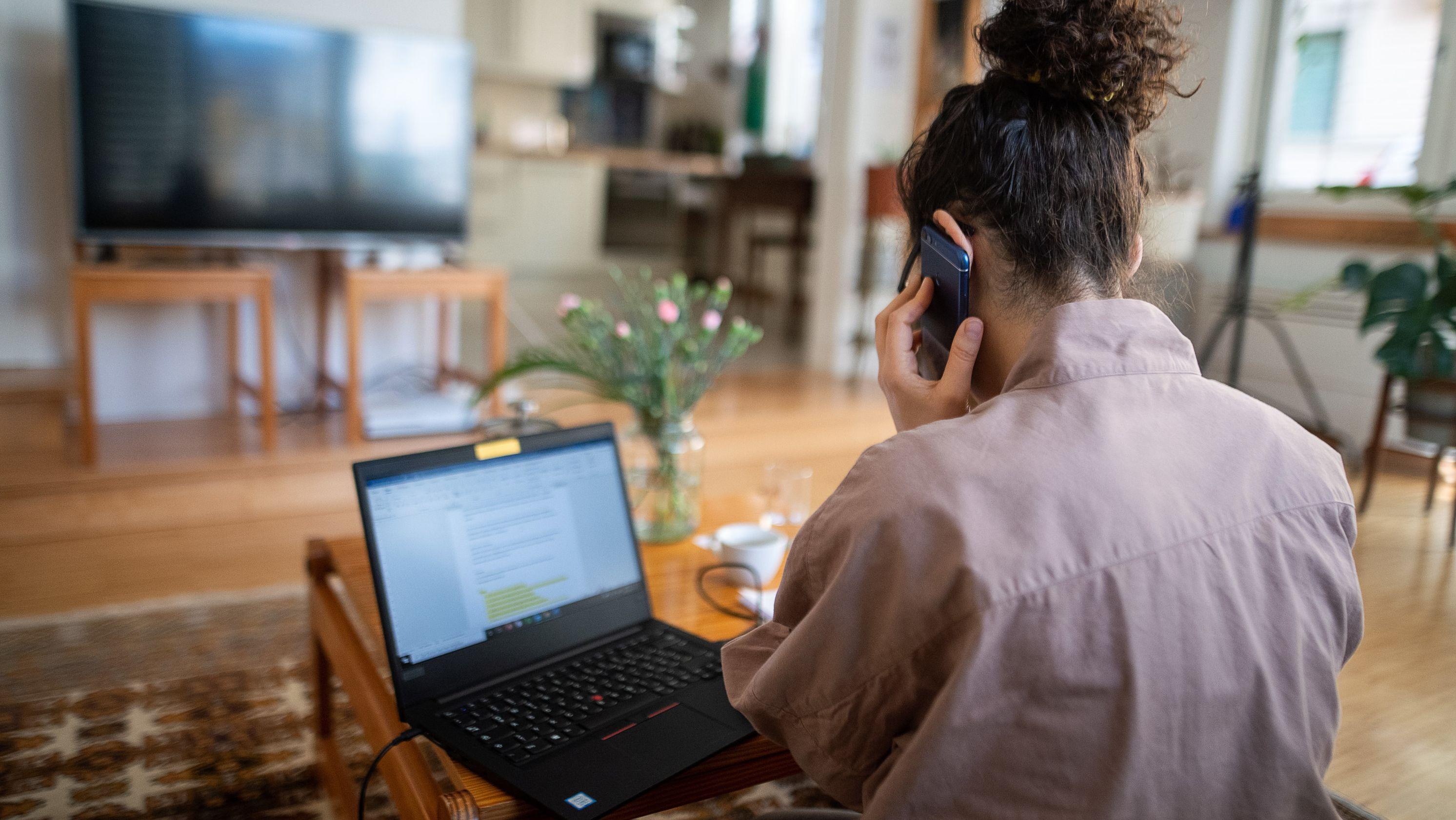 Eine Frau nimmt aufgrund der Ausbreitung des Coronaviruses aus ihrem Wohnzimmer an einer Telefonkonferenz teil und hat einen aufgeklappten Laptop vor sich..