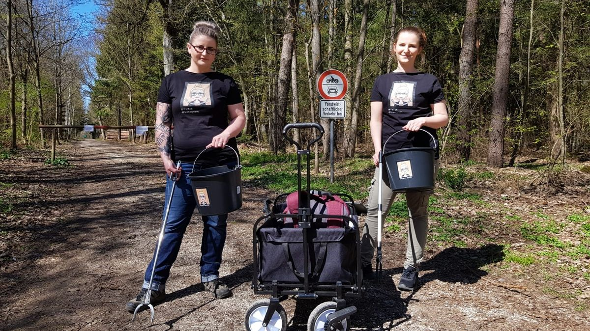 Influencerinnen Liza und Jule stehen mit Eimern, Müllgreifern und einem Bollerwagen auf einem Waldweg