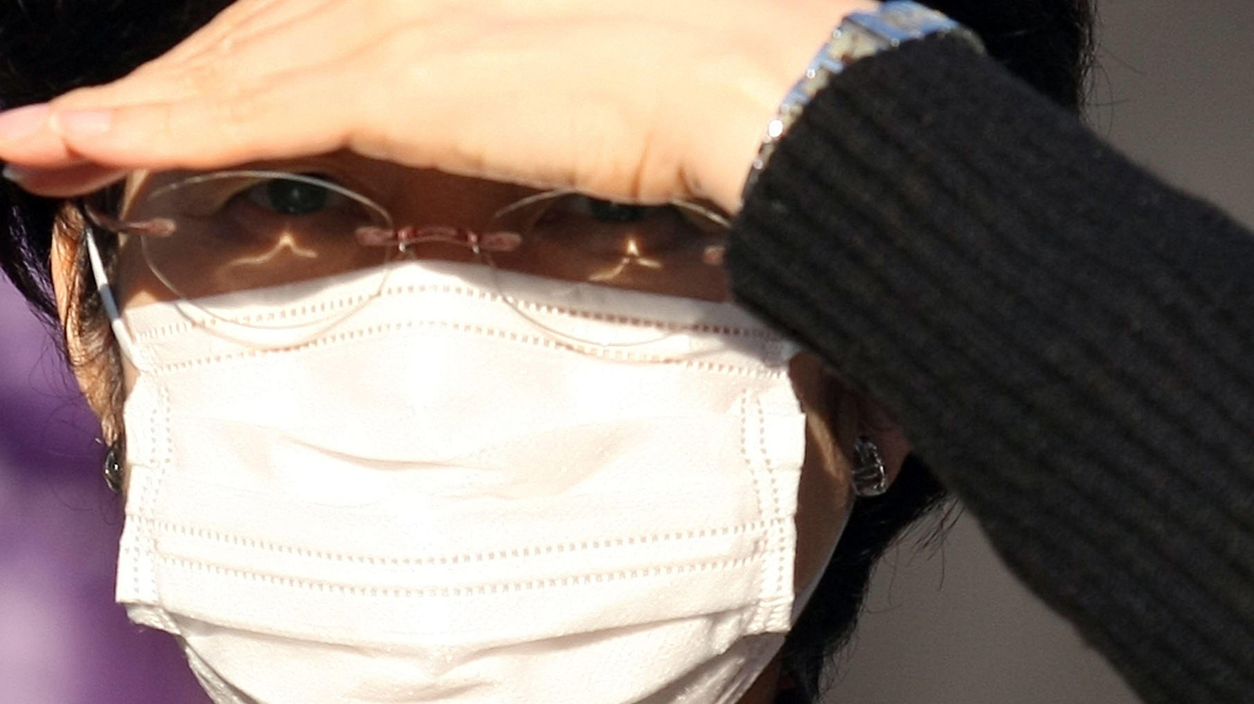 Chinesin trägt eine Atemschutzmaske gegen den Corona-Virus