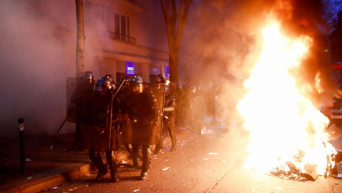 Polizisten gehen in Paris an einem Feuer vorbei, das bei den Ausschreitungen gelegt wurde.