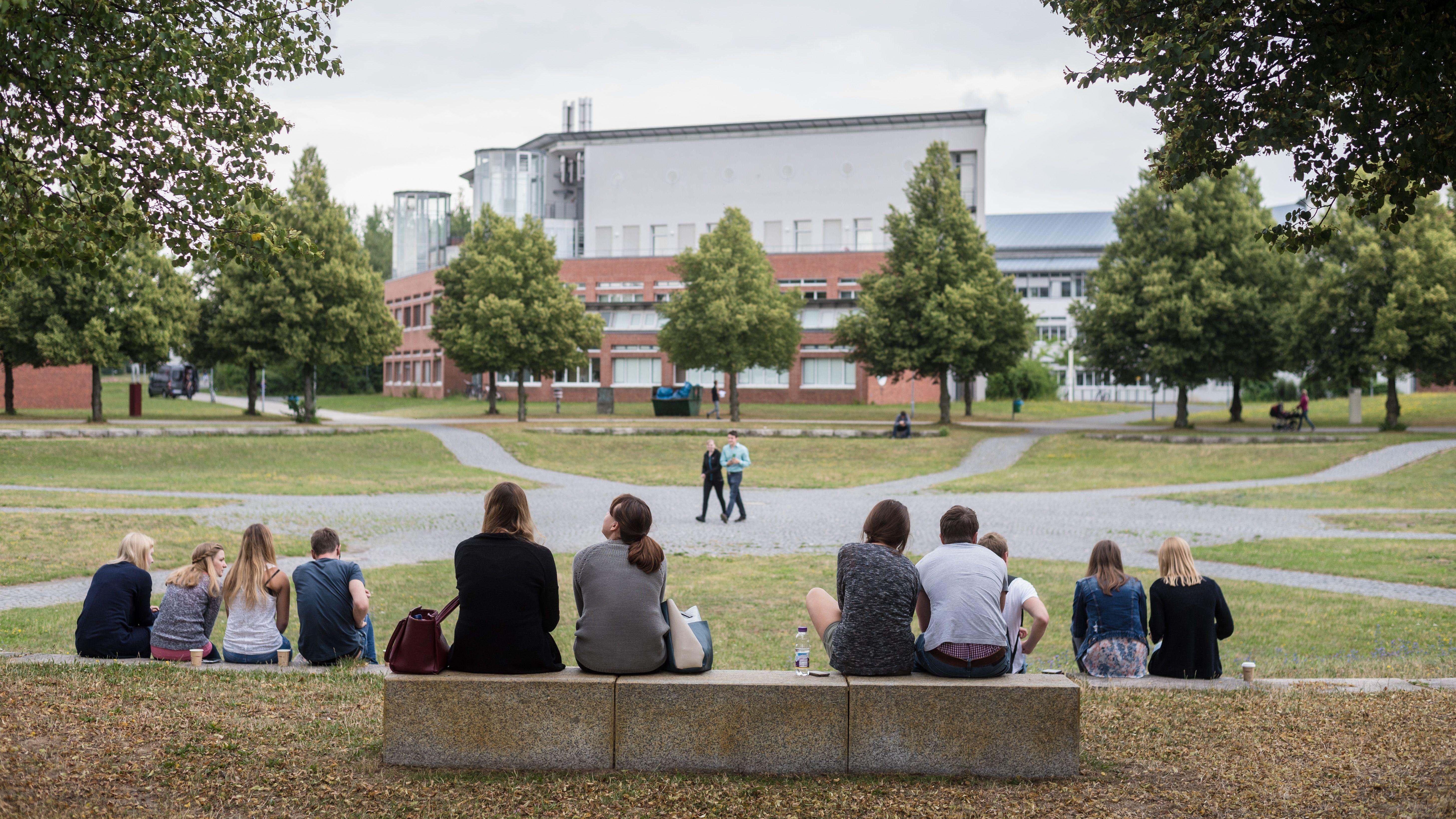 Studenten sitzen auf dem Campusgelände der Universität in Bayreuth zusammen