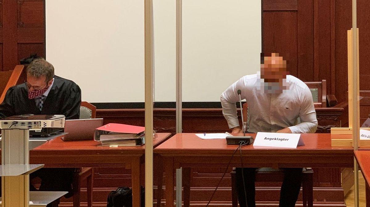 Der Angeklagte trägt ein weißes Hemd, neben ihm sitzt sein Verteidiger in schwarzer Robe.