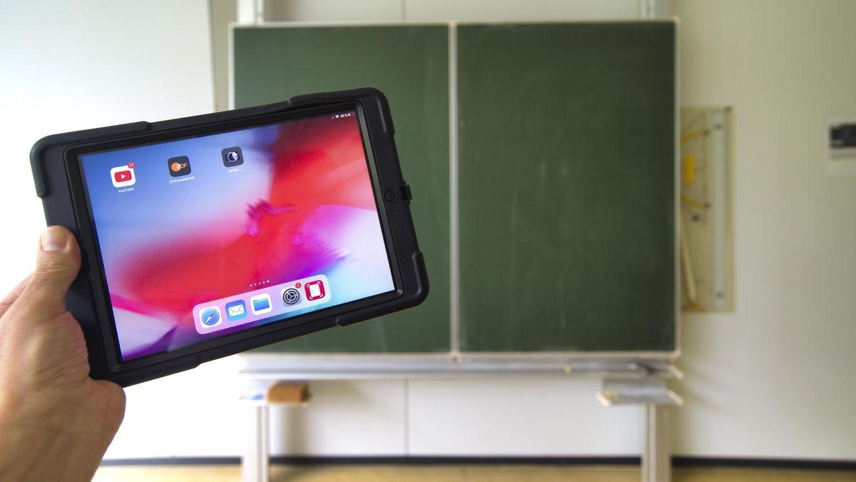 Eine Hand hält ein Tablet vor eine Tafel (Symbolbild).
