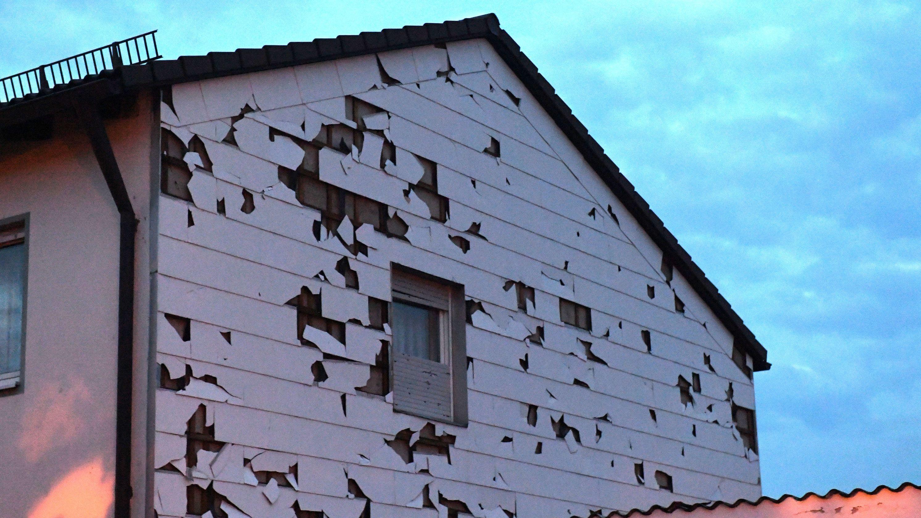 Die Fassadenverkleidung eines Hauses in Germering ist nach einem Hagelsturm durchlöchert.