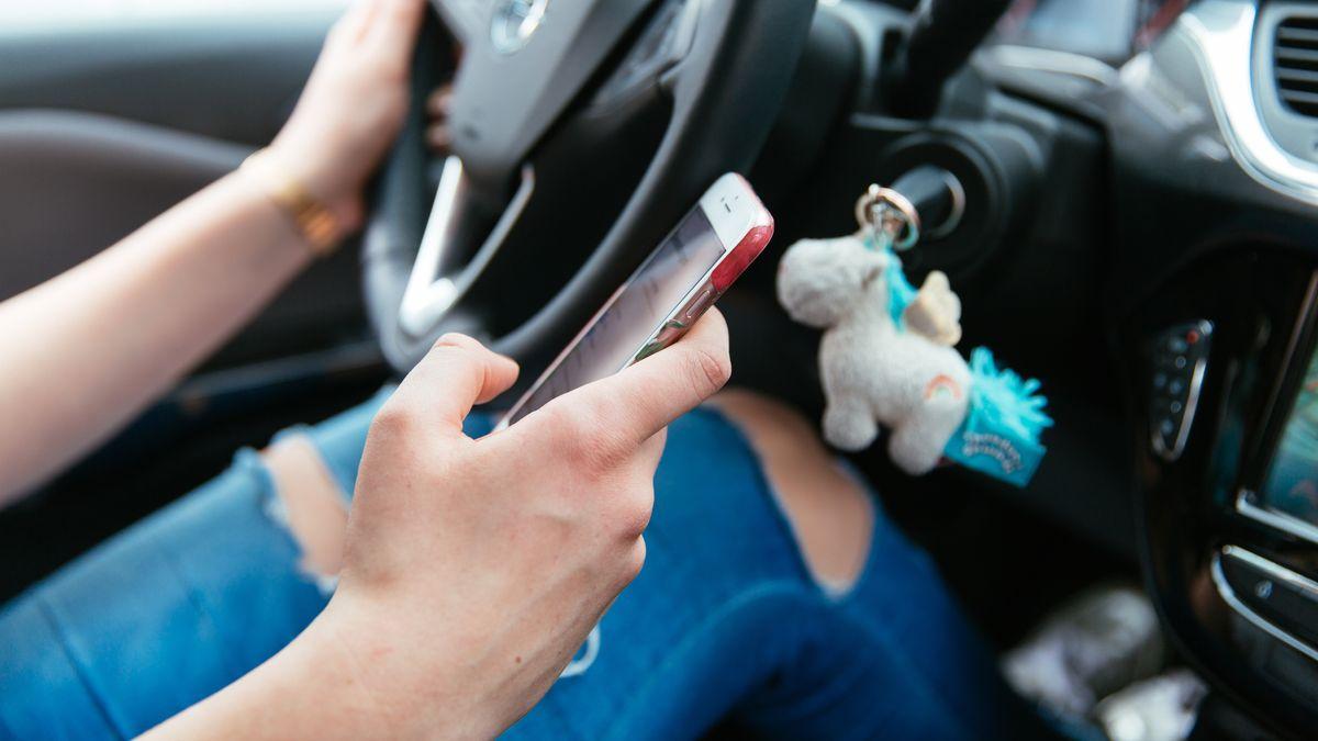 Eine junge Frau benutzt ihr Smartphone während des Fahrens.