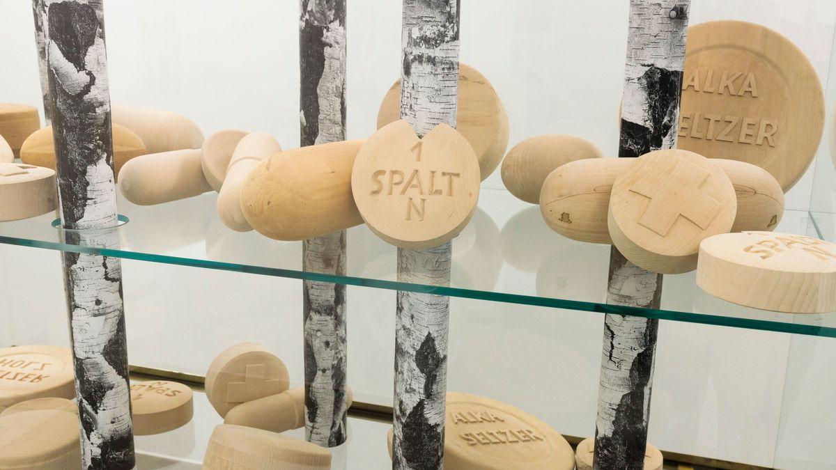 Blick auf ein Kunstwerk von Martin Kippenberger mit Birkenstämmen und überdimensionierten, aus Holz geschnitzten Tabletten