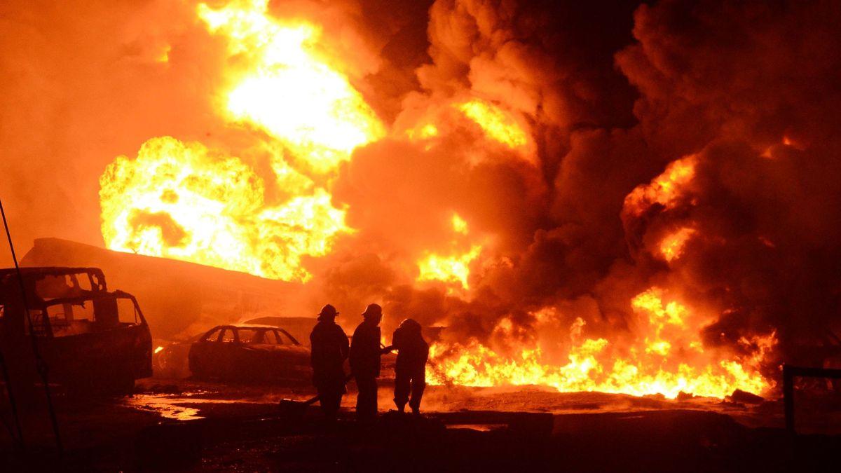 Ein Großbrand nach einer Pipeline-Explosion - im Vordergrund machtlose Feuerwehrleute, in der Bildmitte ausgebrannte Autowracks