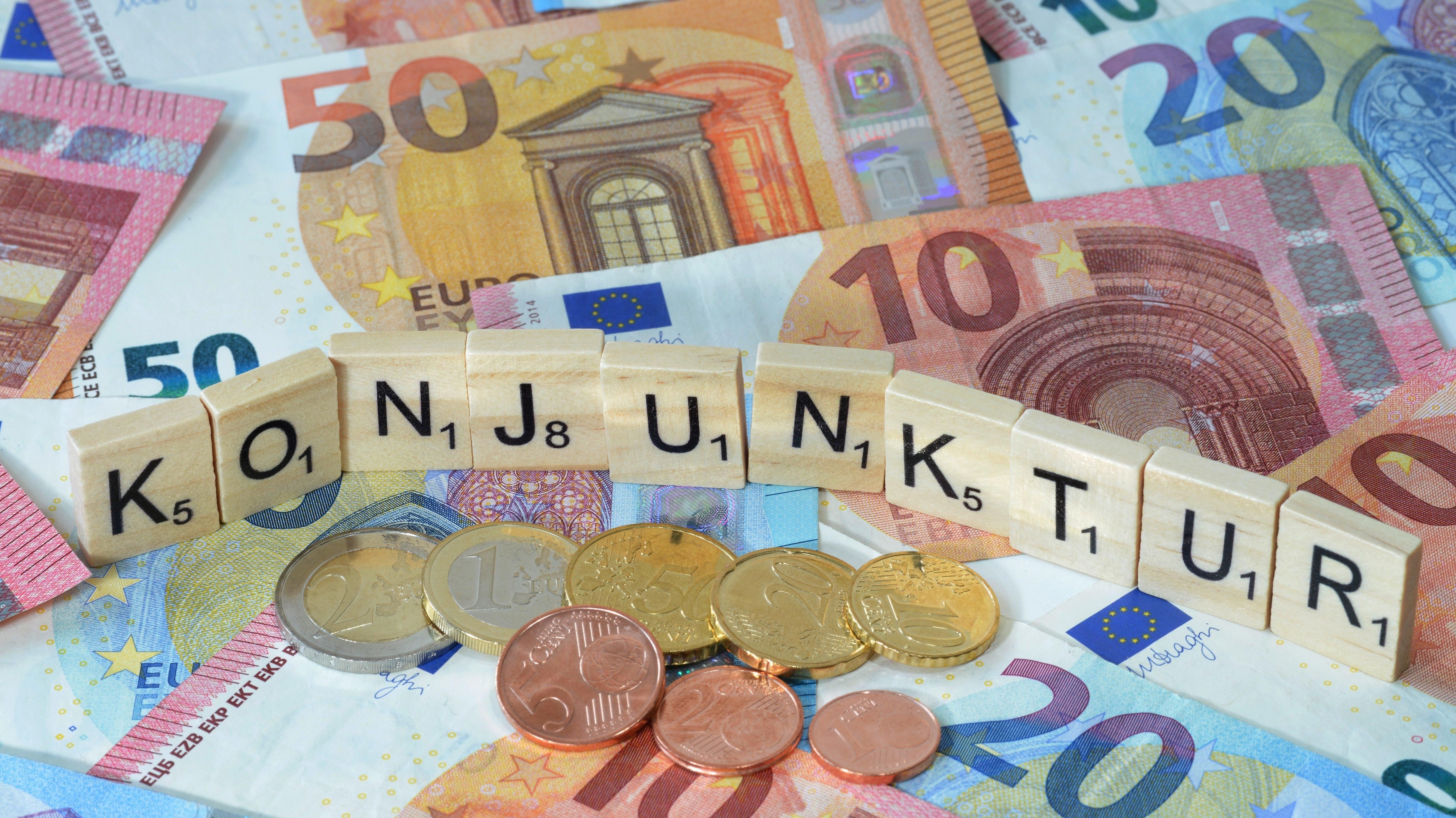 """Scrabblesteine bilden den Schriftzug """"Konjunktur"""" auf Geldscheinen"""