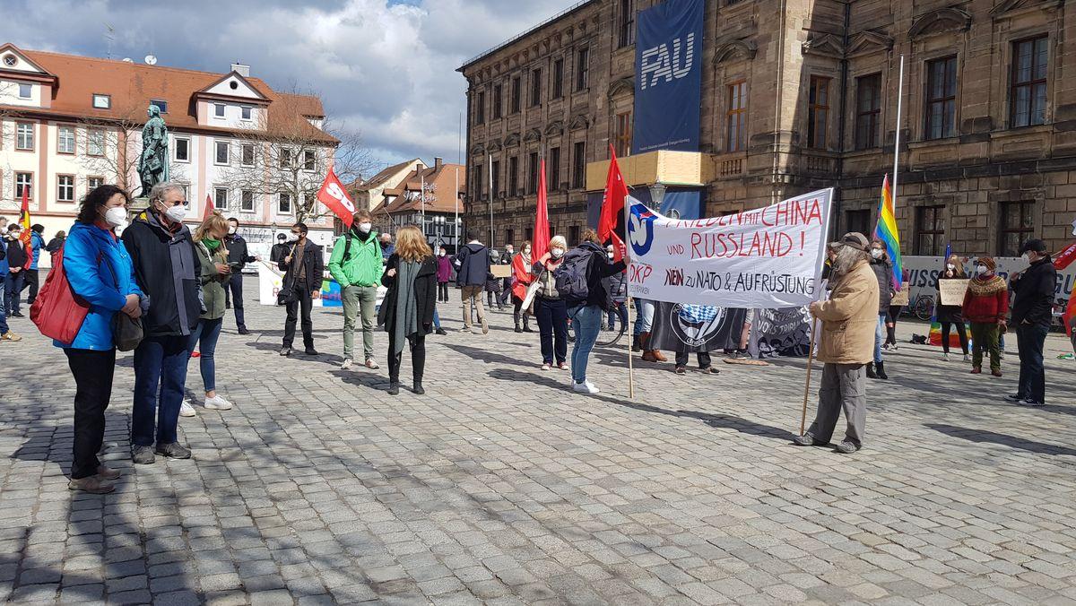 Friedensaktivisten mit Transparenten und Fahnen am Erlanger Schlossplatz