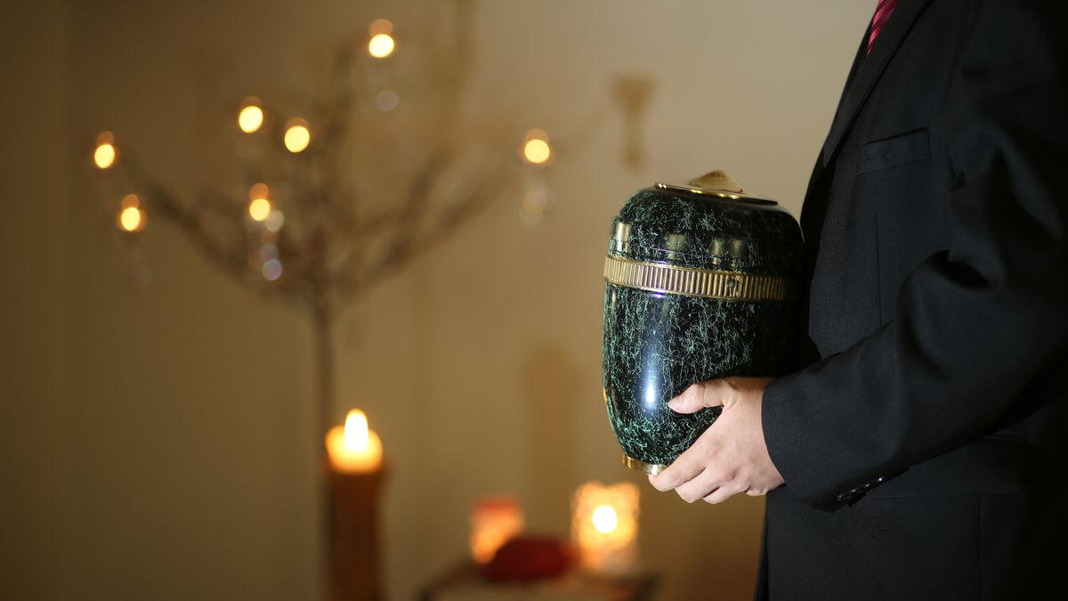 Bestatter hält eine Urne in der Hand