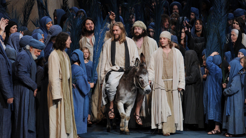 """Der Darsteller Andreas Richter als Jesus (M) reitet in der Fotoprobe zu den Oberammergauer Passionsspielen in der Szene """"Einzug aus Jerusalem"""" auf einem Esel."""