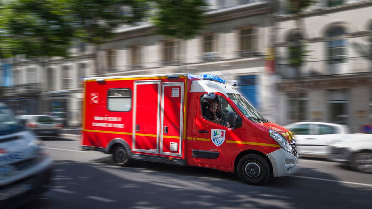 Französisches Einsatzfahrzeug fährt mit Blaulicht durch Straße.