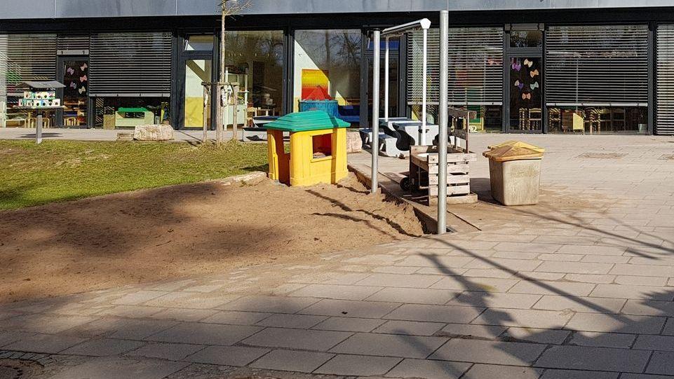 Ein Spielplatz, auf dem ein kleines gelbes Haus mit grünem Dach zum Spielen steht, aber ohne Kinder.