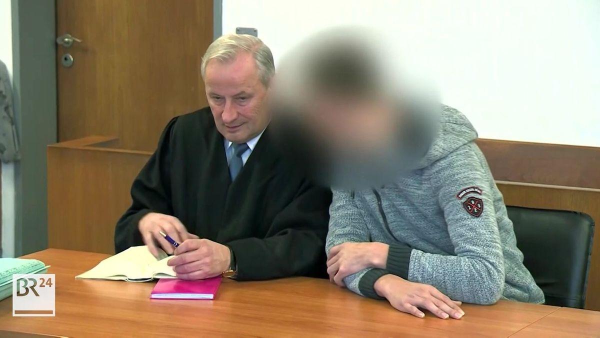 Der Brandstifter von Marktredwitz sitzt auf der Anklagebank neben seinem Verteidiger in schwarzer Anwaltsrobe.