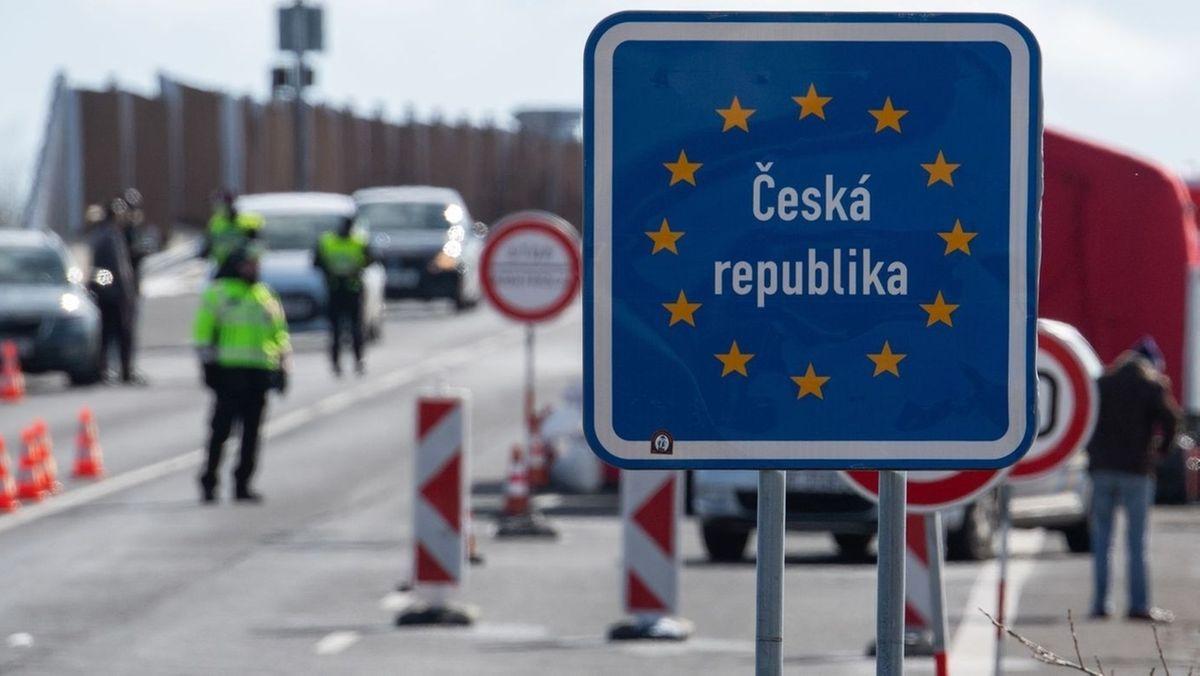 """Ein blaues Schild mit der Aufschrift """"Ceska Republika"""" an der bayerisch-tschechischen Grenze, dahinter Auto, Grenzbeamte und Passanten."""