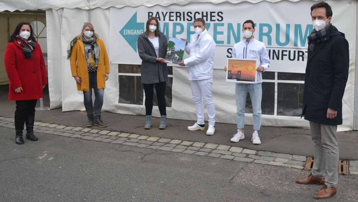 Die Bilderübergabe am Impfzentrum in Schweinfurt mit (von links) Rektorin Nicole Schmitt, Fachlehrerin Christina Düring, Schülerin Laura Hackenberg (alle Balthasar-Neumann-Mittelschule Werneck), Dr. Markus Hüttl, Felix Weisheit (beide Firma 21 Dx) sowie Landrat Florian Töpper.