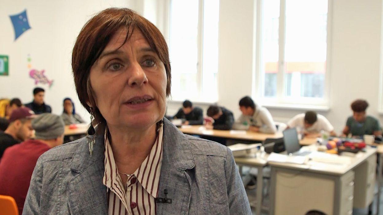 Miriam Herrmann von der SchlaU-Schule steht vor einer Klasse mit jungen Geflüchteten