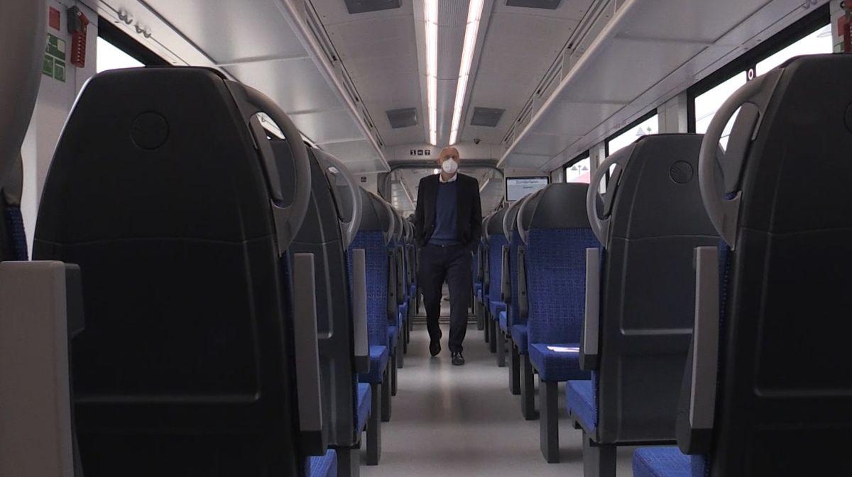Im Inneren eines neuen Zugs steht ein Mann mit Schutzmaske