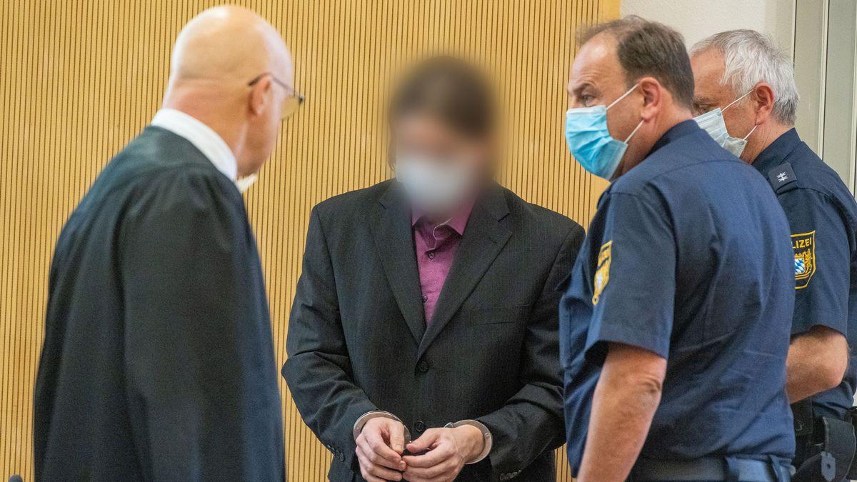 Der Angeklagte (2.v.l.) steht mit Mundschutz im Verhandlungssaal des Landgerichts neben Polizisten und seinem Verteidiger Michael Haizmann