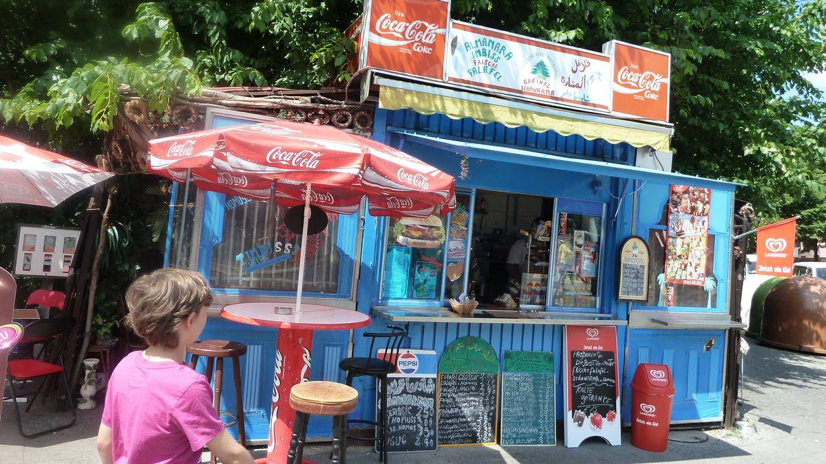 Ein von Migranten betriebener Kiosk, im Vordergrund ein hungriger Passant