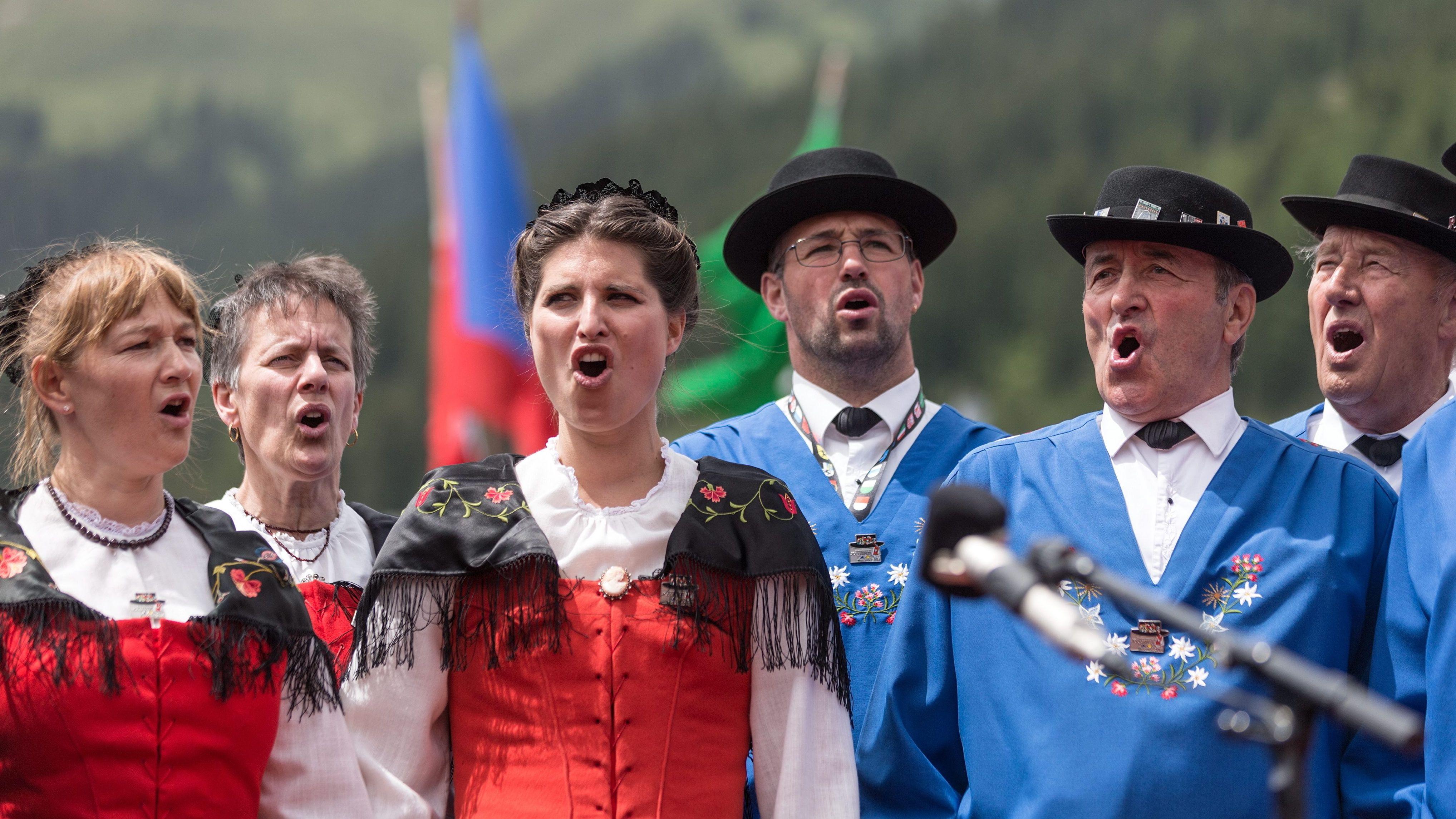 Drei Frauen und drei Männer in Tracht jodeln vor alpiner Kulisse.