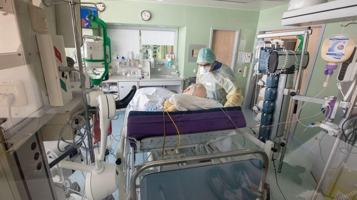 Ein Arzt bei der Visite am Bett eines Corona-Patienten.
