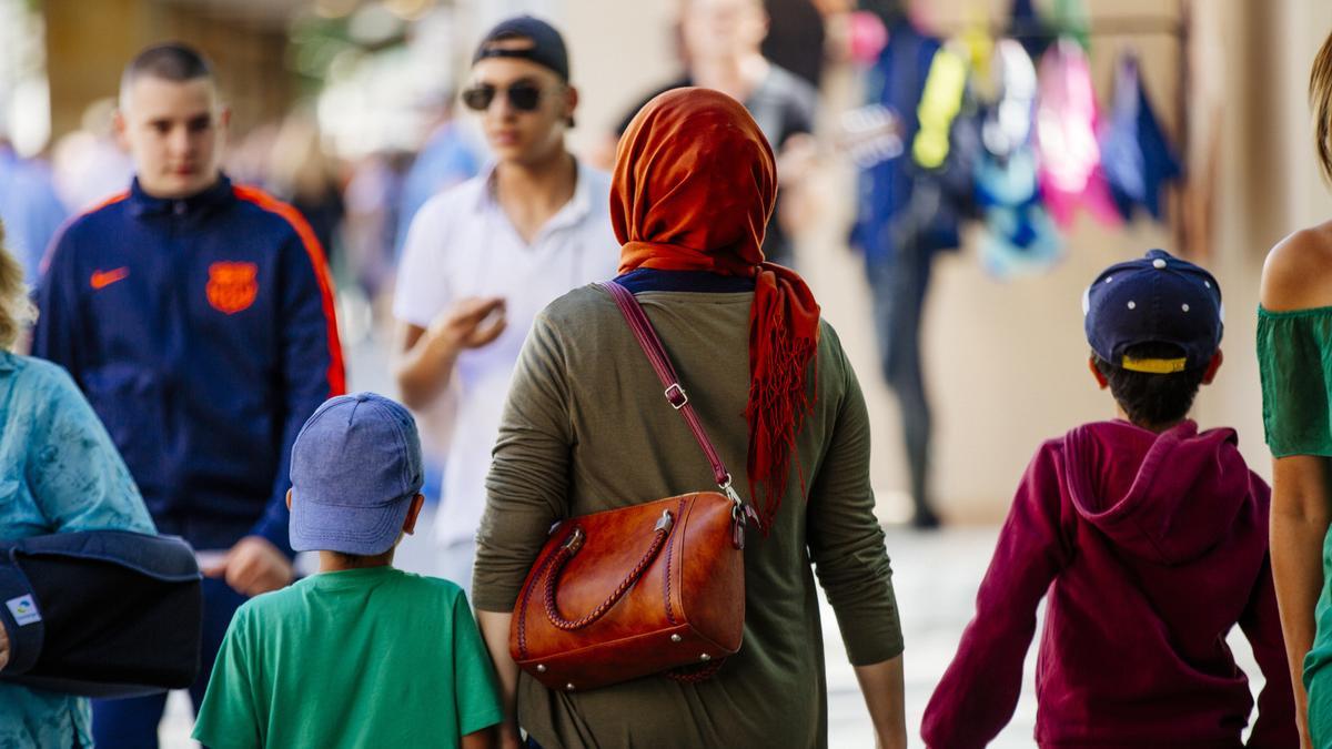Die Fußgängerzone in München. Eine Frau mit Kopftuch und zwei Kindern von hinten, im Hintergrund Jugendliche.