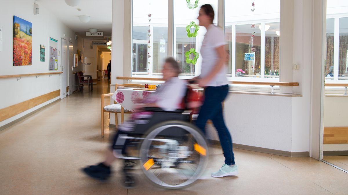 Eine Pflegerin (r) schiebt eine ältere Frau im Rollstuhl durch den Flur eines Seniorenzentrums (Symbolbild)