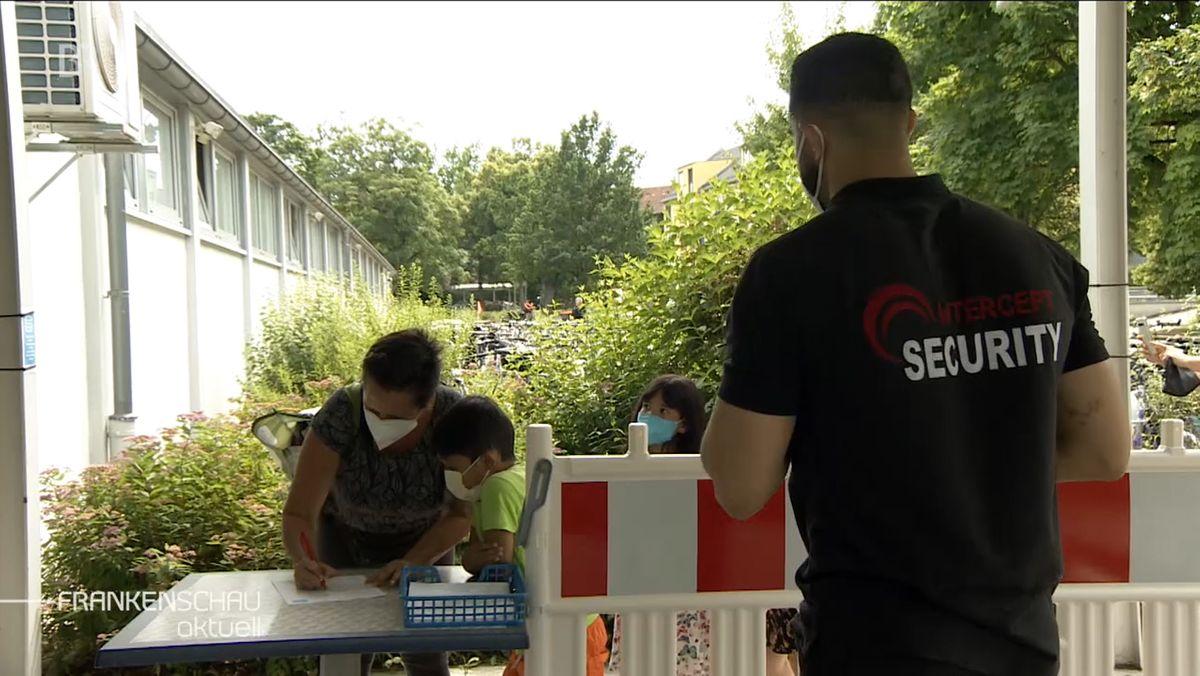 Ein Security-Mitarbeiter steht hinter einer rot-weisen Absperrung. Davor zu sehen sind drei Personen, die ein Blatt auf einem Tisch beschriften.