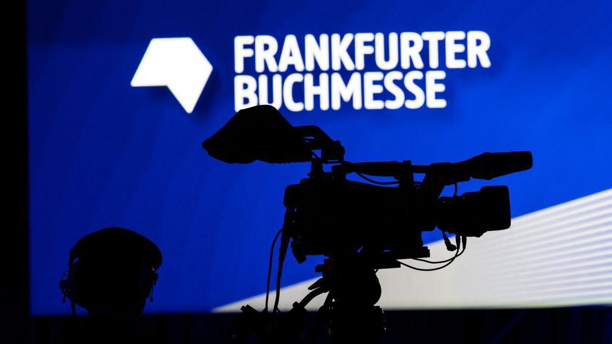 """Schatten einer Kamera vor dem Schriftzug """"Frankfurter Buchmesse"""" auf einem Monitor"""