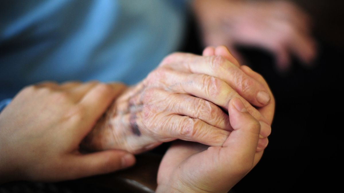 Zwei junge Hände halten die faltige Hand eines alten Menschen.