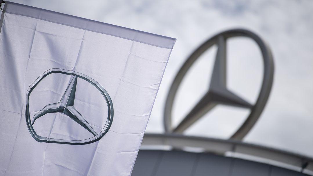 Eine Fahne mit dem Logo der Marke Mercedes-Benz, dem Mercedes-Stern, weht vor einem Showroom der Firma.