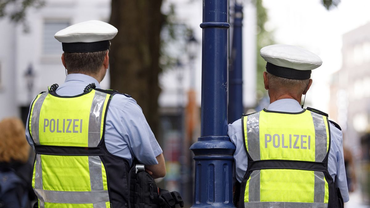 Zwei Polizisten stehen an einer Straße (Symbolbild)