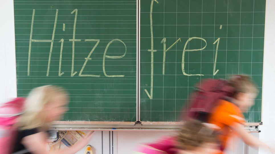 """Schüler einer 2. Klasse laufen in einer Grundschule an einer Tafel mit der Aufschrift """"Hitzefrei"""" vorbei"""