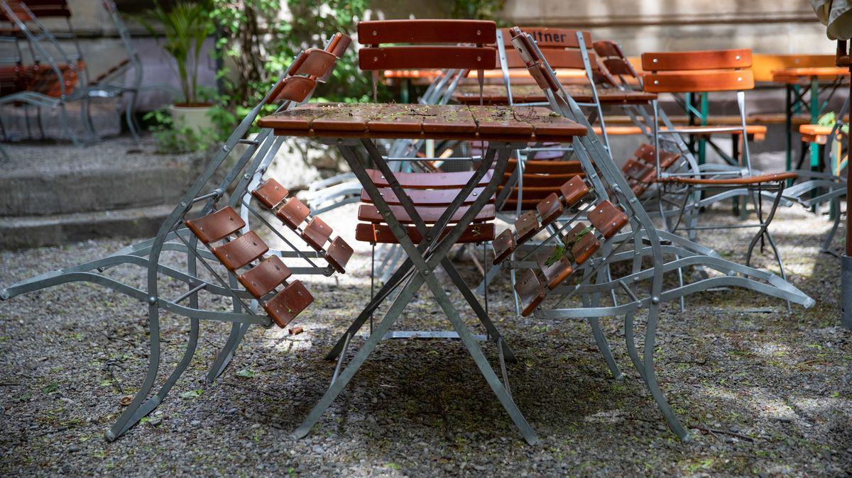 Stühle stehen in einem wegen des Coronavirus noch geschlossenen Biergarten an die Tische gelehnt