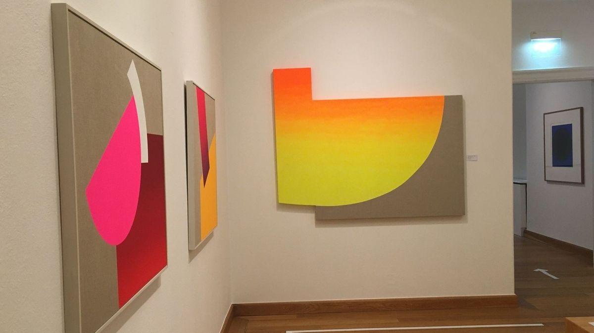 Drei bunte Kunstwerke hängen an einer weißen Wand