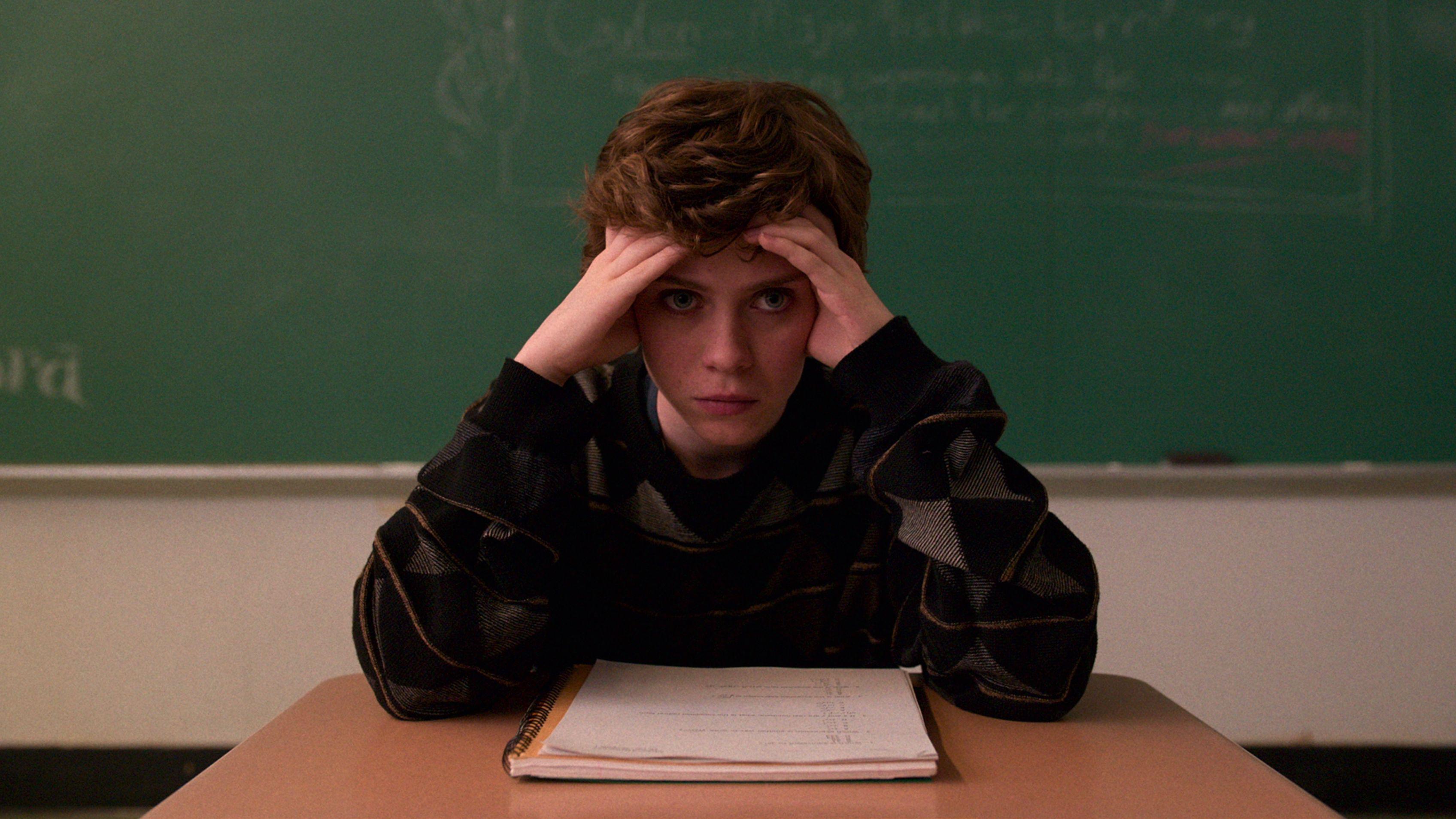 Schauspielerin  Sophia Lillis sitzt in der Schule vor einer Tafel und stützt den Kopf in die Hände