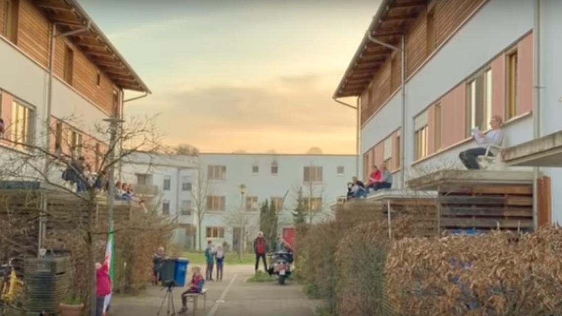 Mehrere Menschen stehen singend in einer Bamberger Wohnhaussiedlung