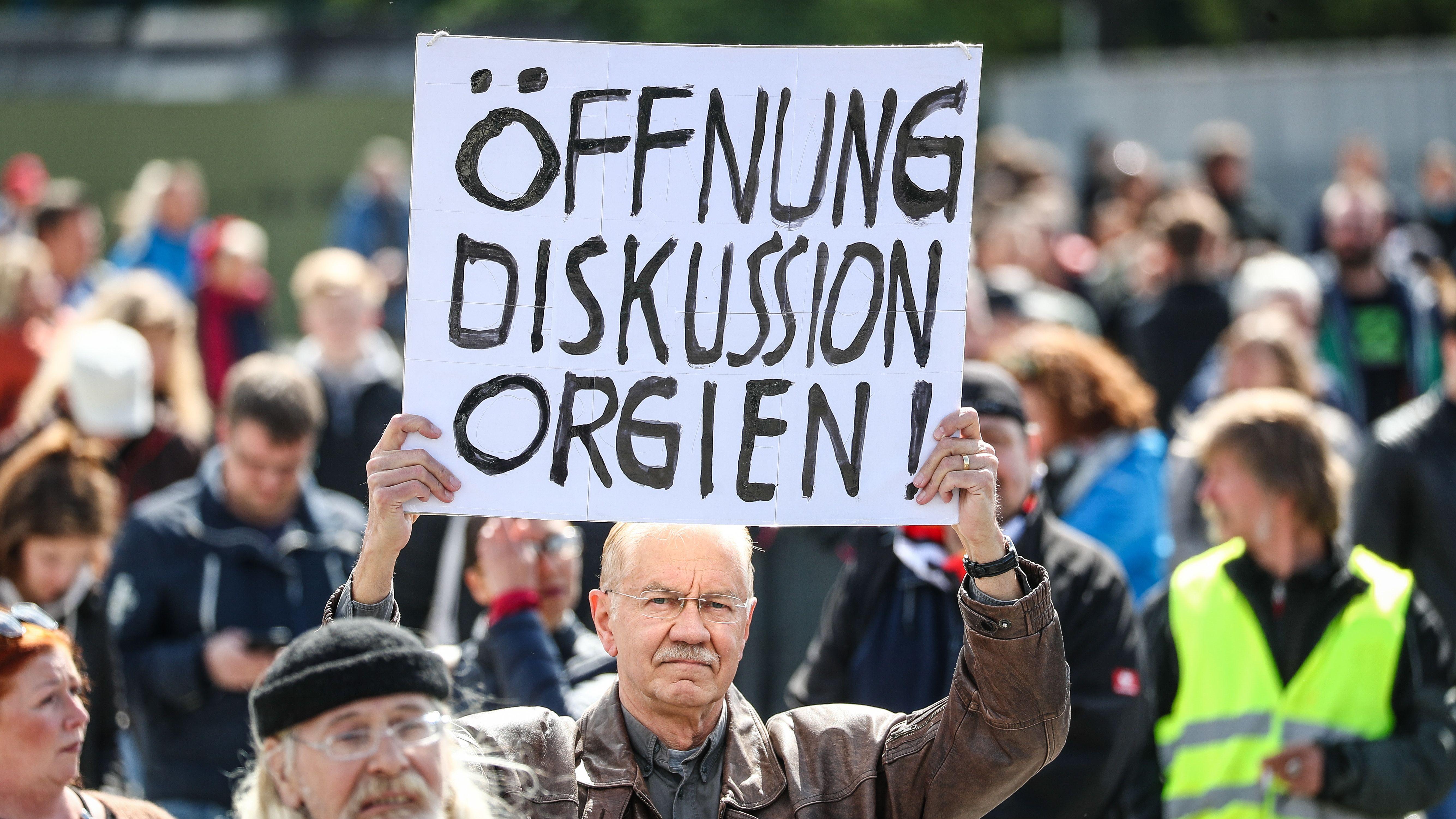 """""""Öffnung Diskussion Orgien!"""" steht auf dem Schild eines Teilnehmers einer Protestkundgebung in Stuttgart gegen die Corona-Beschränkungen."""