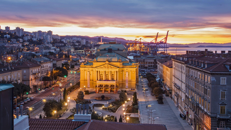 Blick auf den Platz vor dem angestrahlten Nationaltheater im Zentrum von Rijeka in der Dämmerung