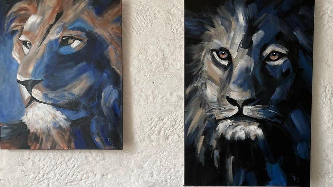 Bilder von zwei Löwen an einer weißen Wand.