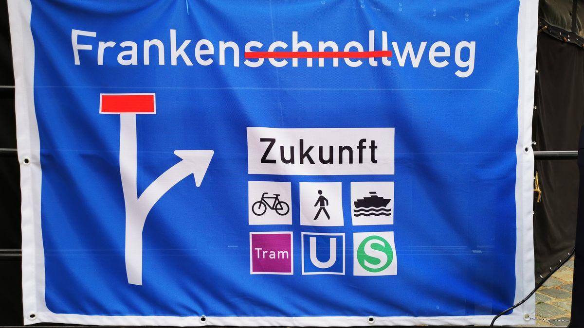 """Blaues Banner mit der Aufschrift Frankenschnellweg, das """"Schnell"""" ist durchgestrichen."""