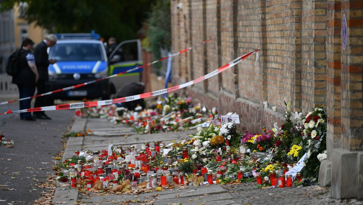 Blumen und Kerzen stehen neben einer Mauer der Synagoge in Halle, vier Tage nach dem rechtsextremistischen Anschlag auf die Gemeinde, dahinter steht ein Polizeiwagen.