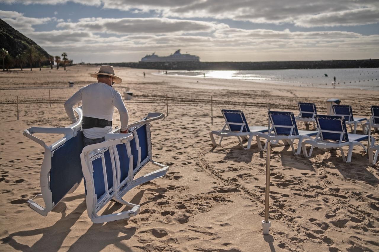 Dezember 2020, Spanien, Tenerriffa: Ein Mann stellt Liegestühle am Strand von Las Teresitas in Santa Cruz de Tenerife auf.