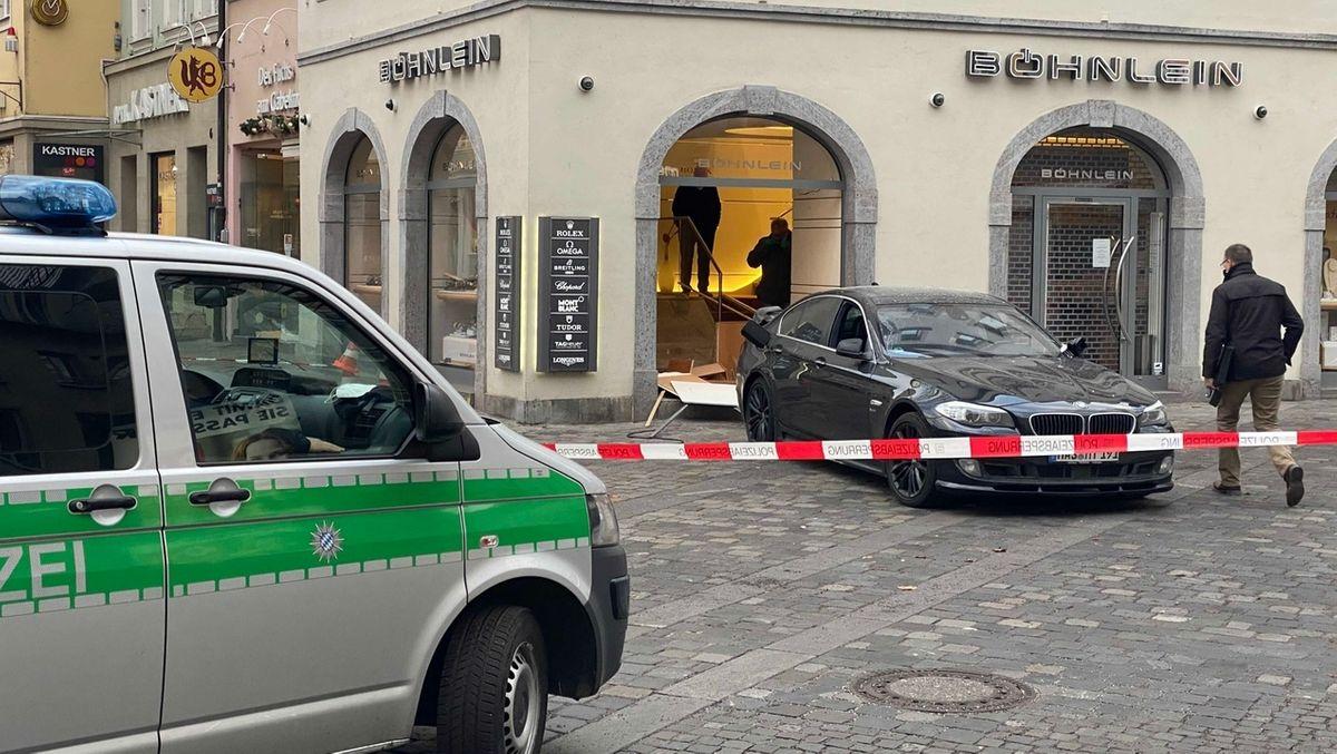 Ein schwarzer BMW steht mit dem Heck in einem Juwelierladen.