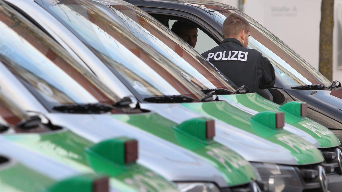 Polizeifahrzeuge und Polizist (Symbolbild)
