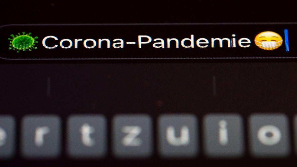 """""""Corona-Pandemie"""" steht auf dem Display eines Mobiltelefons."""