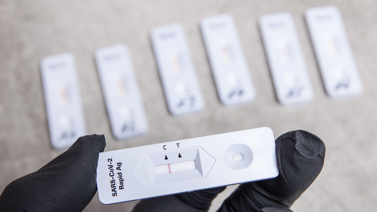 Eine Person mit Schutzhandschuhen hält eine Testkassette von einem negativen SARS-CoV-2 Rapid Antigen Test in der Hand.